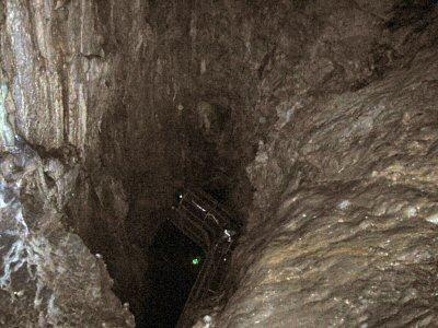 帰路の「三原山」上から見下ろす第一地底湖。 はるか下に逆「く」の字型にあるのが、第一地底湖ホールの通路の屋根。 つまりこれは、巨大な竪穴を見下ろしているのである。
