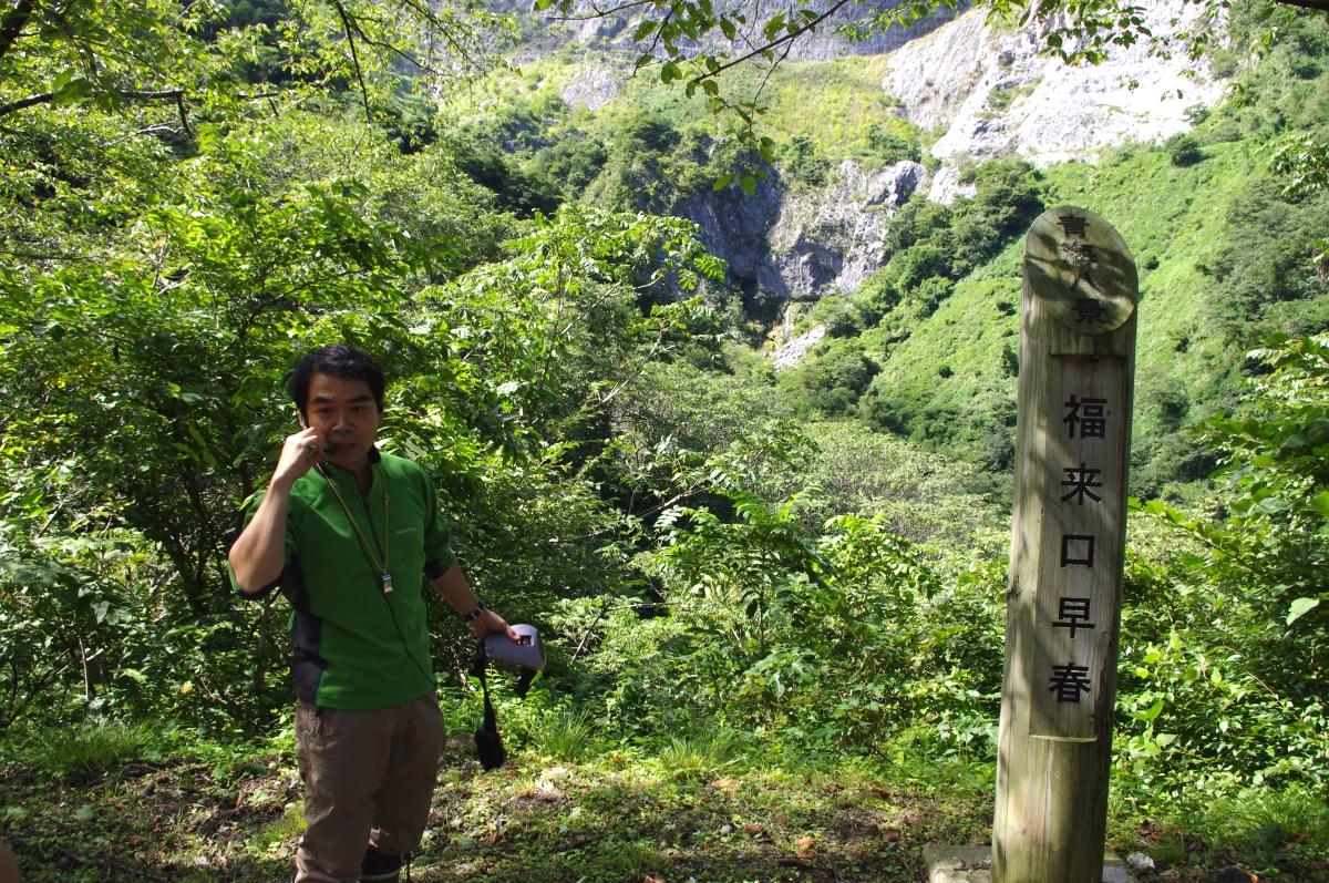 福来口鍾乳洞を望む向かい側でネイチャーガイドさんの説明。 糸魚川フォッサマグナミュージアムの学芸員をされている方。